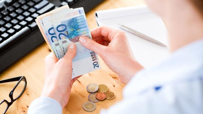 Persona trabajando con billetes de euros