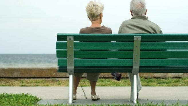 Una pareja de ancianos, sentados en un banco.