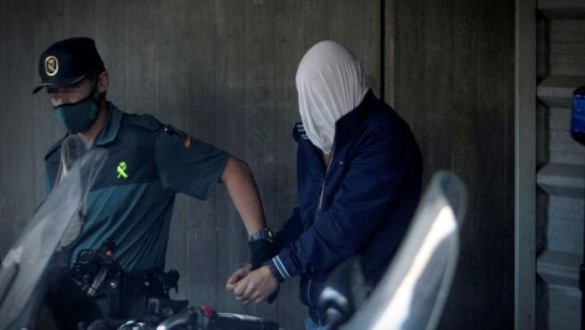 Uno de los presuntos culpables del asesinato de Samuel Luiz es conducido a un furgón de la Guardia Civil.
