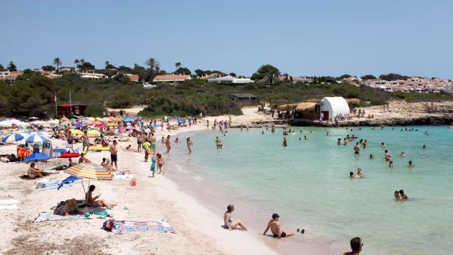 La playa de Binibèquer de Menorca llena de gente este domingo, jornada en la Aemet ha decretado alerta amarilla por las altas temperaturas.
