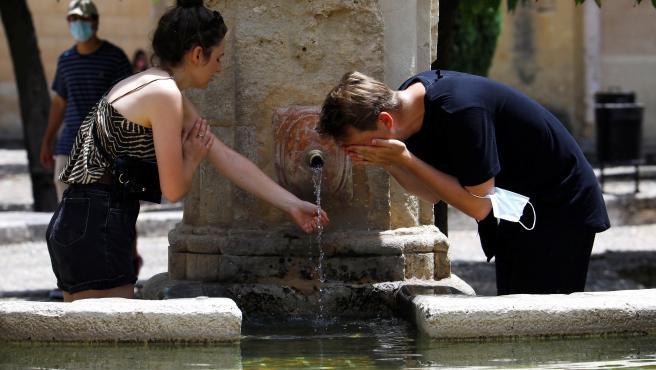 Varis personas se refrescan en una fuente de Córdoba para intentar sofocar las altas temperaturas este fin de semana.