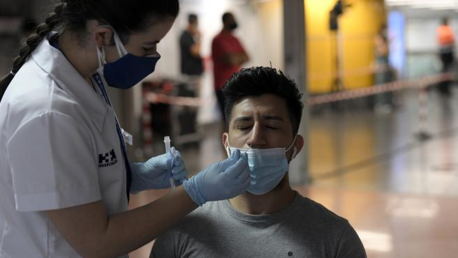 Una sanitaria realiza un test de antígenos a un hombre, en un dispositivo de realización de test de antígenos en el intercambiador de Plaza de Castilla, a 2 de julio de 2021, en Madrid (España)