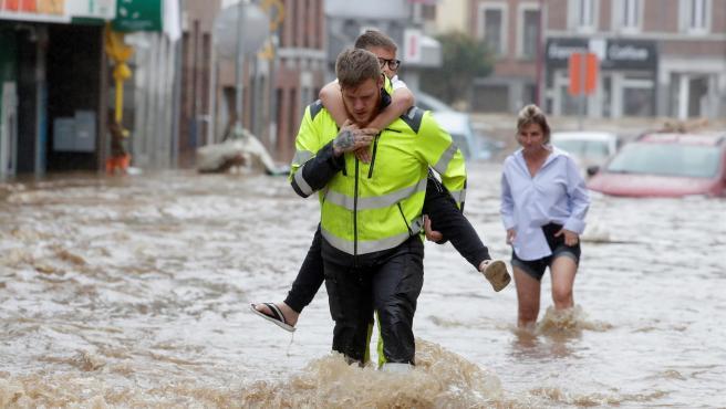 Tras las inundaciones y los derrumbes sufridos en el área de Ensival, un hombre ayuda a una mujer y su hijo a cruzar una calle.