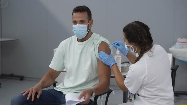 Un joven recibe la primera dosis de la vacuna Pfizer en el Hospital Zendal.