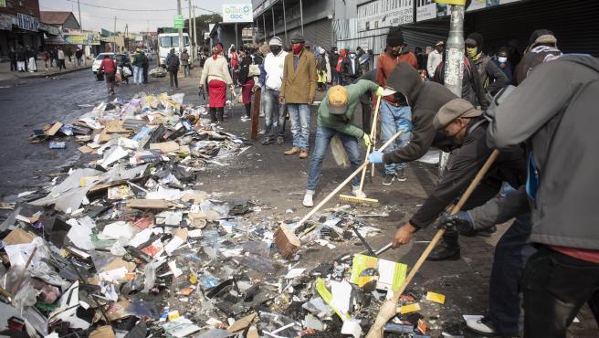 Los residentes locales limpian las calles después de los saqueos en grandes almacenes y tiendas en Johannesburgo.