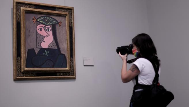 Una mujer realiza una fotografía de la obra 'Busto de mujer, de Pablo Picasso
