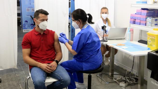 La enfermera Mercè Costas administra la dosis número 500.000 de Fira de Barcelona, punto de vacunación masivo de la Covid-19, ante la mirada de la administrativa Ariadna Martín; quien la recibe es Òscar Parra, de 31 años.
