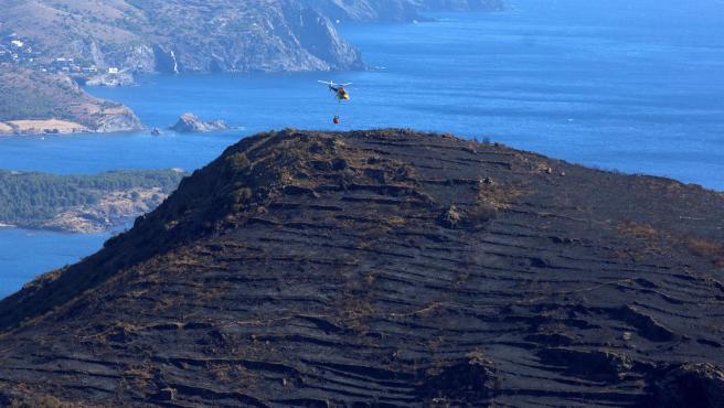 Un helicóptero se dispone a refrescar la superficie afectada por el quemada por el incendio del parque natural de Cap de Creus.