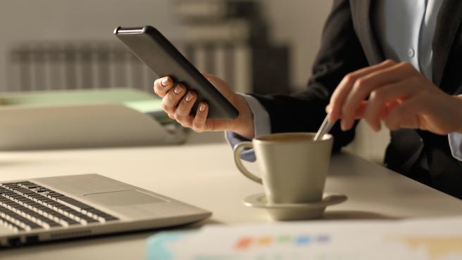 Una persona mira su móvil mientras se toma un café y trabaja.