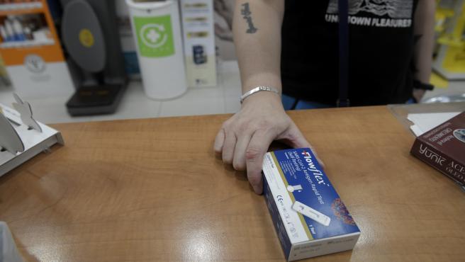 Un client mostra un test d'antígens de detecció del COVID-19 en una farmàcia.