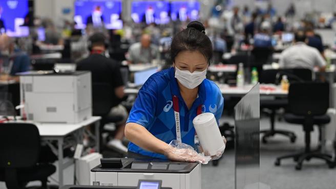 Una empleada realiza labores desinfección por la pandemia de covid-19, en el centro olímpico de medios de comunicación, en Tokio.