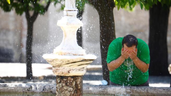 Un hombre se refresca en la fuente de los naranjos de la Mezquita - Catedral de Córdoba.