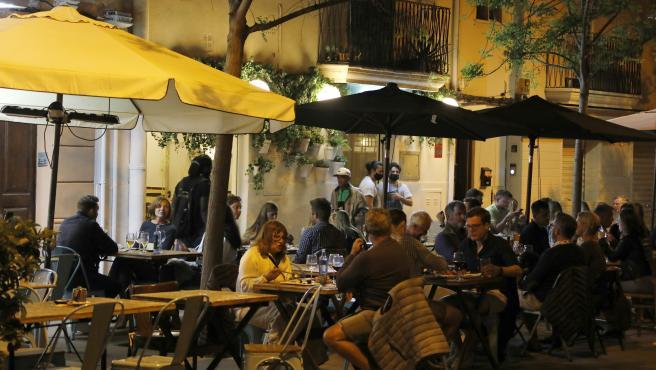 Gente en un bar de Palma por la noche.