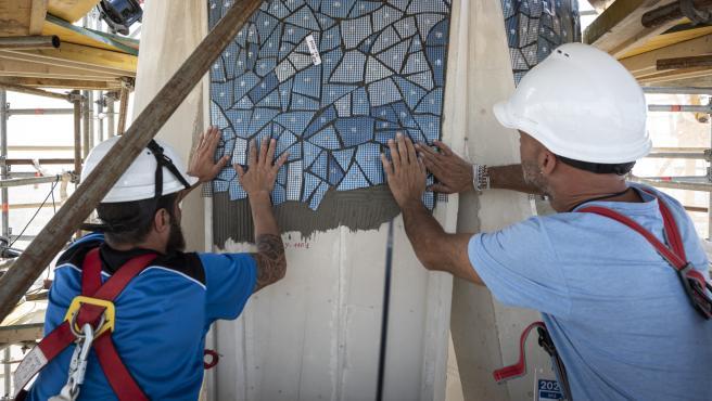 Unos operarios instalan el 'trencadís' que ornamenta la Torre de María de la Sagrada Familia de Barcelona.