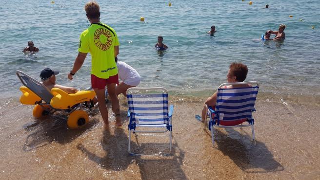 Socorristas en Sant Antoni de Calonge ayudando a una persona mayor a entrar en el agua.