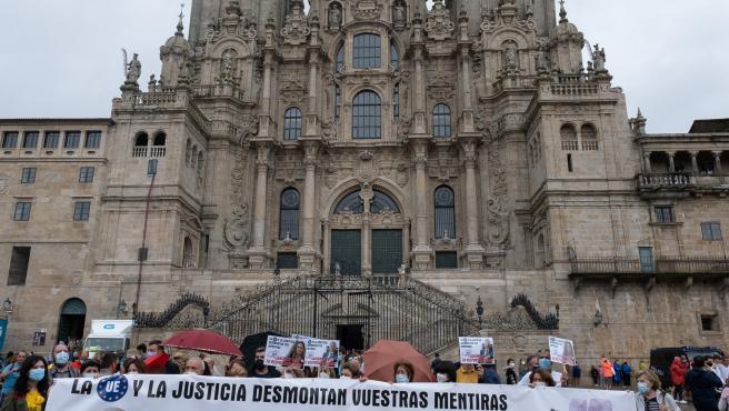 Familiares víctimas del Alvia portan una pancarta frente a la catedral De Santiago como protesta en el aniversario del accidente.