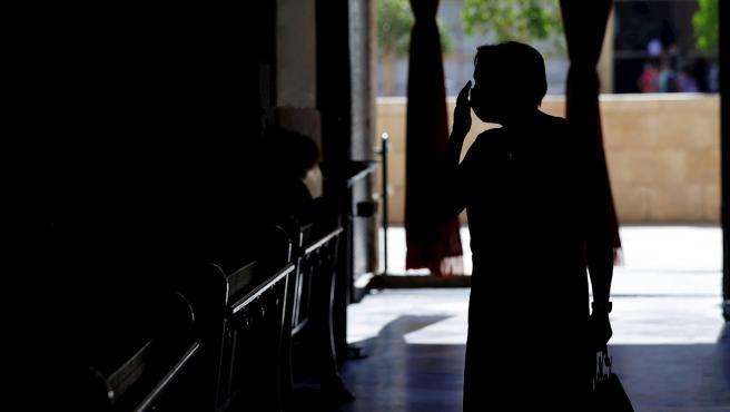 Una mujer, protegida con una mascarilla, se santigua al entrar en la Basílica de Valencia.