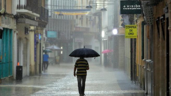 Un hombre camina, este lunes, bajo una intensa lluvia por el centro de la ciudad de Gandía, en Valencia.