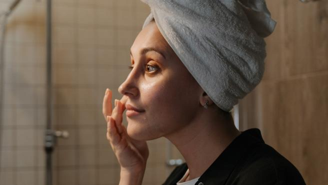 Una mujer se aplica productos cosméticos en el rostro.
