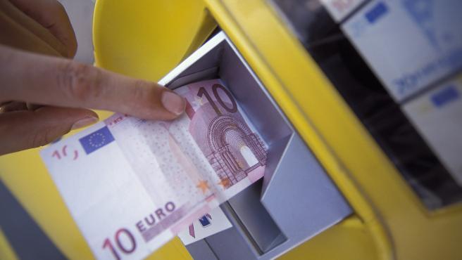 Una persona retira 10 euros de un cajero automático.