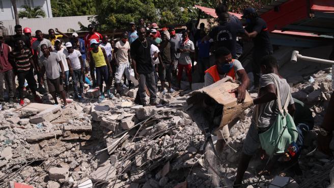 Imágenes de haitianos rebuscando en los escombros.