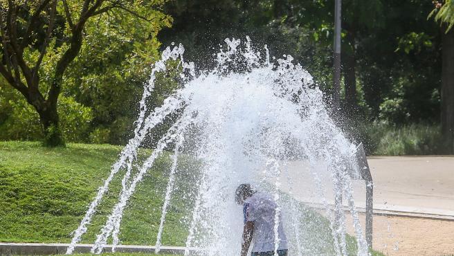 Un niño se moja en una fuente en el parque de Madrid Río.