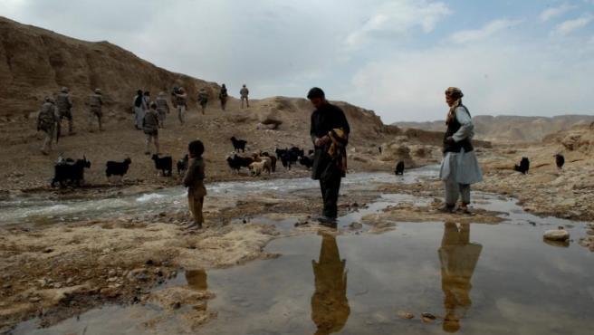 Un grupo de militares patrulla por las montañas junto a unos campesinos afganos.