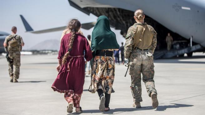 Una integrante del cuerpo de la Marina estadounidense acompaña a dos niñas para evacuarlas en el aeropuerto de Kabul.
