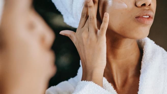 Una mujer se aplica una crema facial, en una imagen de archivo.