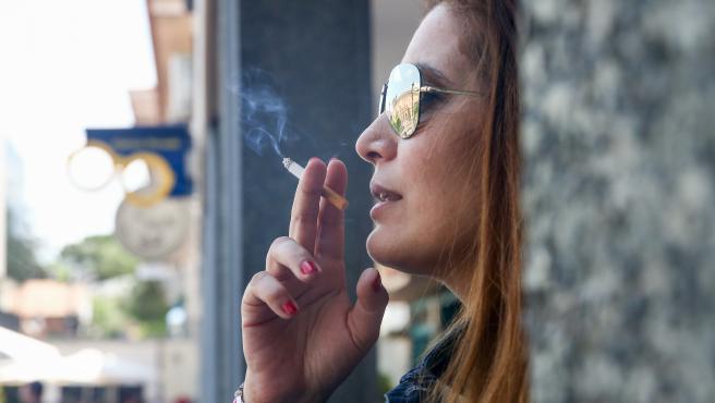 Una mujer fumando un cigarro.