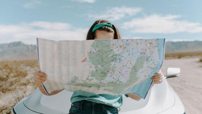 Chica mirando un mapa en la carretera