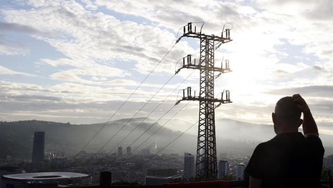 Un hombre observa el cableado de la red eléctrica en Bilbao.