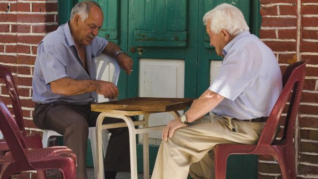 Dos ancianos juegan en la calle.