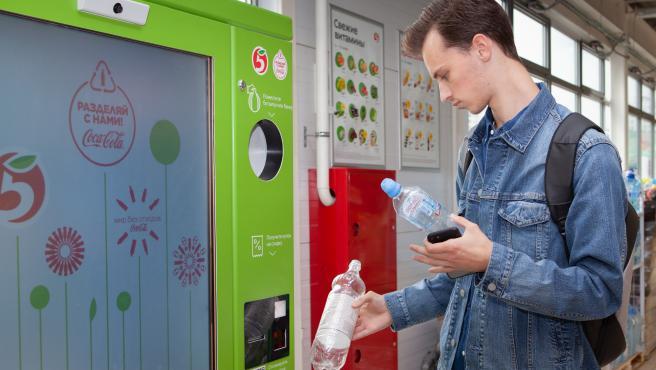 Un joven introduce envases de plástico en una máquina Reverse vending en Moscú