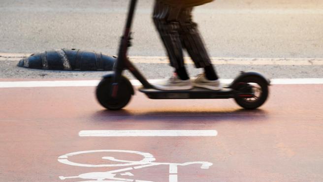Un patinete eléctrico circulando en un carril bici.
