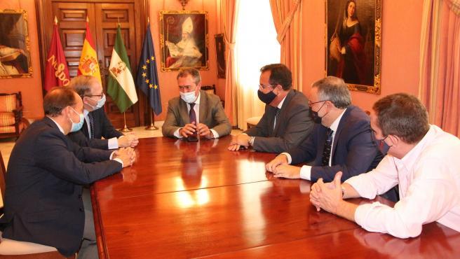 El alcalde, Juan Espadas, y el delegado de Fiestas Mayores, Juan Carlos Cabrera, en una reunión con el presidente del Ateneo de Sevilla, Alberto Máximo Calero.