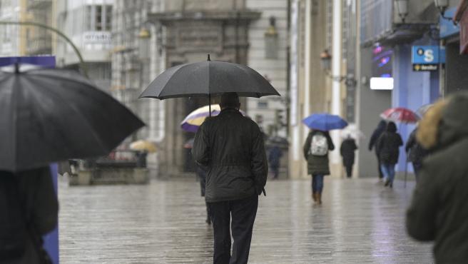 A Coruña Temporal de lluvia y viento  Personas con paragüas en la zona del Obelisco 20/01/2021 Foto: M. Dylan / Europa Press