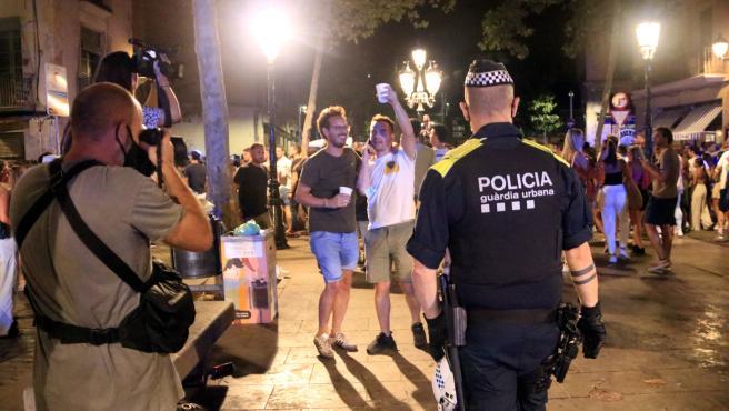 Un agente de la Guardia Urbana de Barcelona delante de personas haciendo botellón, este verano.