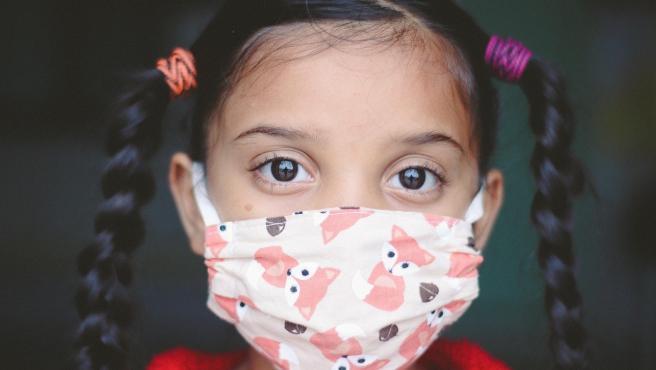 Una niña con mascarilla.