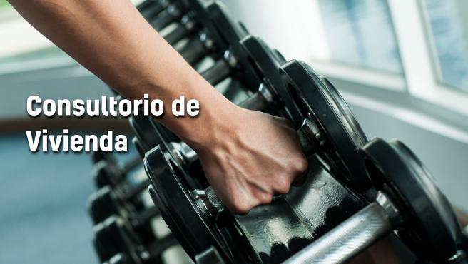 Un hombre coge una pesa en un gimnasio.
