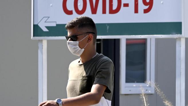 Un hombre con mascarilla por el coronavirus pasa junto a una clínica en Skopje, Macedonia del Norte.