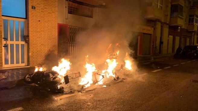 Sucesos.-Un incendio calcina tres ciclomotores, dos motocicletas y afecta a varios vehículos en la zona norte