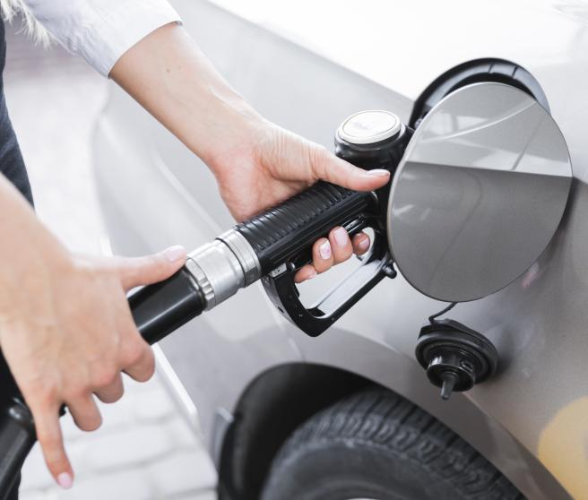 Mujer llenando el depósito de su coche en una gasolinera