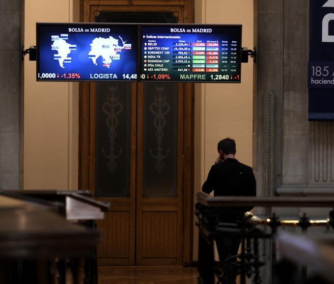 Una persona camina bajo los televisores indicativos con los valores del Ibex en el Palacio de la Bolsa de Madrid.