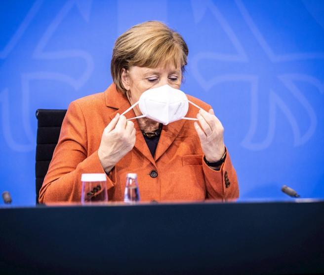 La canciller alemana, Angela Merkel, se retira la mascarilla para dirigirse en una rueda en la que ha anunciado un confinamiento duro para Alemania.