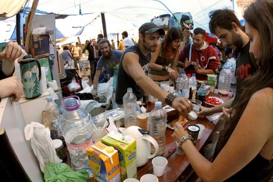 Varios jóvenes comiendo en el campamento que han organizado los asistentes a la protesta de Sol.
