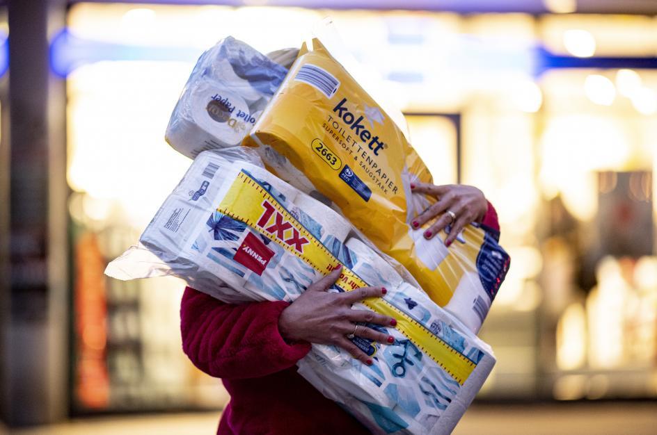 Una mujer carga con varios paquetes de papel higiénico en plena pandemia.