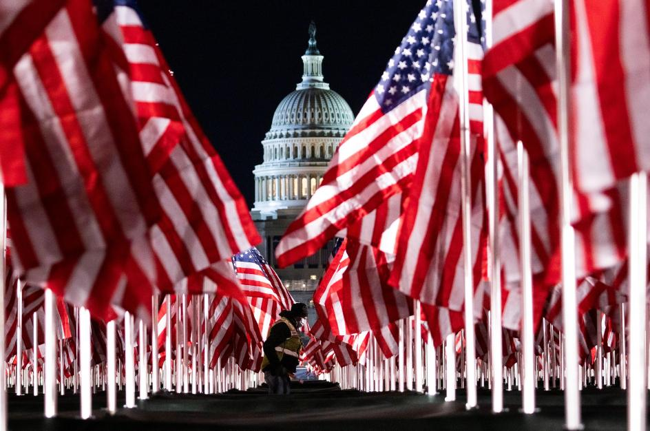 Una persona pasa entre las 200.000 banderas instaladas frente al Capitolio para la investidura de Biden. Las banderas representan a los estadounidenses que no podrán acudir a la ceremonia de investidura del nuevo presidente de los Estados Unidos