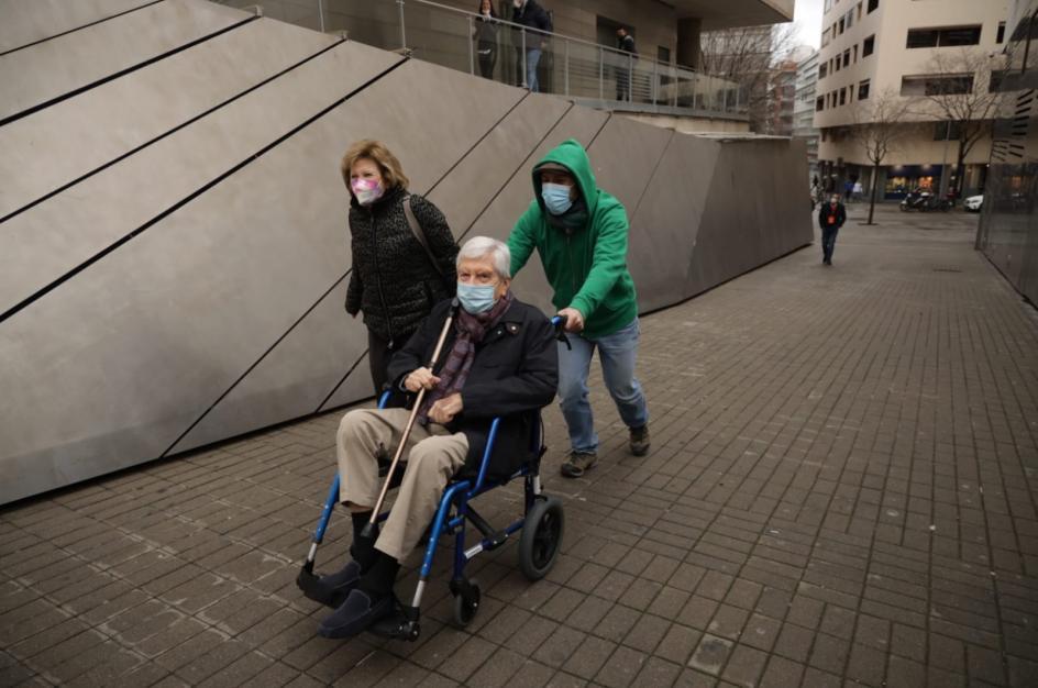 Un anciano en silla de ruedas es llevado a votar en el auditorio Axa de Barcelona.