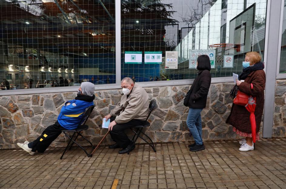 Algunas personas, como estos ancianos, optaron por sentarse para hacer cola. La imagen está tomada en la puerta del polideportivo Creueta del Coll de Barcelona.